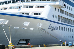 Bow of cruise ship at dock. Seattle, WA, USA July 15, 2016: Bow of Oceania Cruise ship Regatta docked at Pierr 66 terminal in Seattle with worker doing Royalty Free Stock Photography