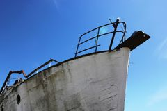 Bow of a derelict boat. The bow of a derelict boat against a blue sky in a dockyard on the UK south coast. The paintwork and the metalwork on the boat is Stock Photography