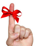 Bow on finger. Red bow on finger isolated over white background Stock Photography