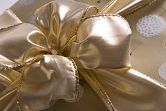 Bow of Gold. Gold fabric bow tied on a package of matching gold and white wrapping paper Stock Photography