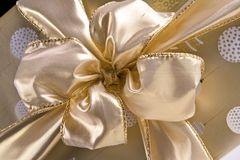 Bow of Gold. Gold fabric bow tied on a package of matching gold and white wrapping paper Stock Photo