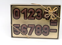 Bow golden box. Filled with chocolate numbers Stock Image