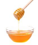 Bow of honey and wooden spoon. Stock Photos