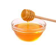 Bow of honey and wooden spoon. Stock Photo