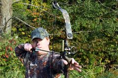 Bow hunter. Pulls back a compund for a shot Royalty Free Stock Photography