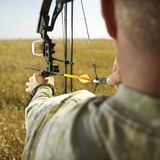 Bow hunter with compund bow. Bow hunter in field pulling back arrow on compund bow Stock Photos