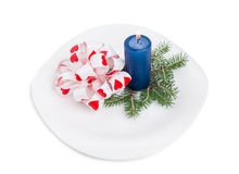 Bow-knot with fir branch and blue candle. Royalty Free Stock Image
