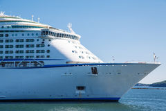 Bow of Luxury Cruise Ship in Blue Water. Huge, white, luxury cruise ship anchored in blue water Royalty Free Stock Images