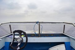 The bow of the motor boat with the steering wheel floating on the river stock image
