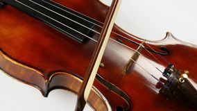 The bow moves along the violin strings. Brilliant beautiful wood of the violin deck. Closeup stock video footage