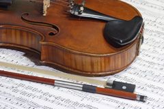 Bow and notes. Old violine in detail with a note sheet in background Royalty Free Stock Photos