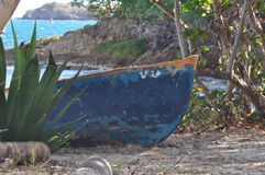 Bow of an old blue boat on an island. Bow of an old blue boat on the island of St. Croix. It is on the beach with trees around and the sea in the background royalty free stock photos