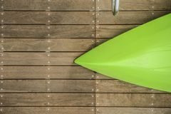 Bow of overturned green kayak laying on a natural wood dock with part of a chrome handrail at side Stock Photography