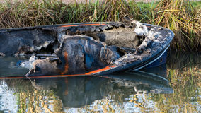 Bow of partially submerged canal boat after fire. Damaged hull of narrow boat in Kennet and Avon Canal after being gutted by fire Royalty Free Stock Photo