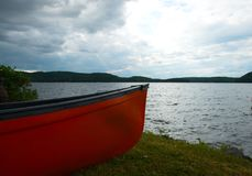 Bow of a red canoe on a grassy shore with lake royalty free stock photo
