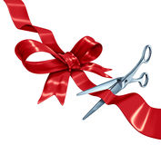 Bow And Ribbon Cutting. With a red silk gift wrapping decoration with scissors opening the present packaging as a holiday symbol for Christmas a birthday or stock illustration