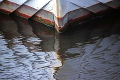 Bow of a ship of wood reflected in the water surface, abstract b Royalty Free Stock Photo
