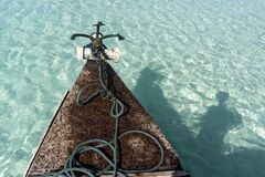 Free Bow Side Of Traditional Zanzibar Dhow Boat With Anchor And Rope At The Shallow Beach Water With Shade Of Sailor Royalty Free Stock Images - 200341599