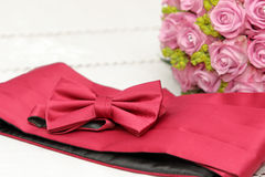 Bow tie and belt for the groom on bridal bouquet background Royalty Free Stock Image