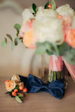 Bow tie and boutonniere. On a wooden table Stock Photos