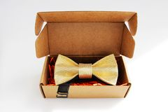Bow tie in a cardboard gift box. color gold