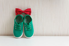 Bow tie and green shoes on background wall with wallpaper Stock Image