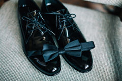 Bow-tie and male shoes. Black bow-tie and black male shoes Royalty Free Stock Image