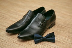 Bow tie and man's shoes. Black bow tie and black man's shoes Royalty Free Stock Photography