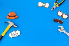 Bow tie, moustache, glasses, hat and instruments for rapair for Happy Father Day on blue background top view mokeup. Bow tie, moustache, glasses, hat and stock photo