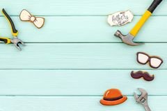 Bow tie, moustache, glasses, hat and instruments for Happy Father Day on mint green background top view mokeup stock photo