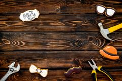 Bow tie, moustache, glasses, hat and instruments for rapair for Happy Father Day on wooden background top view mokeup royalty free stock image