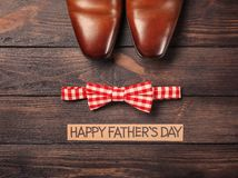 Bow tie and pair of male shoes on wooden background. Father`s day composition Stock Images
