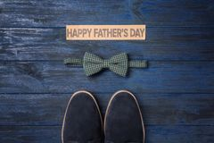 Bow tie and pair of male shoes on wooden background. Father`s day composition Royalty Free Stock Photos