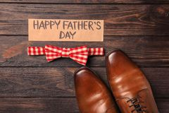 Bow tie and pair of male shoes on wooden background. Father`s day composition Stock Photo