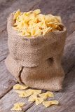 Bow Tie Pasta Dry in sackcloth bag on the old table closeup Stock Photography