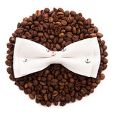 Bow tie patterned sea anchor lie on the circle of coffee beans isolated Royalty Free Stock Image