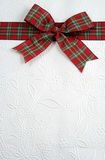 Bow On Top. A plaid christmas bow on decorative white paper Stock Photo