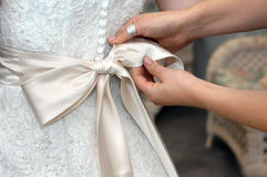 Bow Tying. Hands tie the satin bow of wedding gown.  Closeup of female hands looping ties into elegant bow Stock Photography