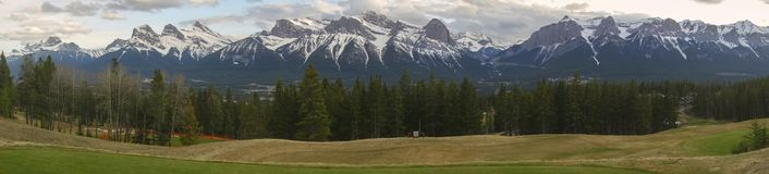 Bow Valley Canmore Alberta Foothills Wide Panoramic Landscape. Wide Panoramic Springtime Landscape of Snowcapped Mountains above Bow Valley in Canmore Alberta Stock Photo