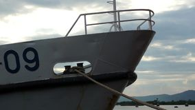 Bow of white ship tied down to the dock in the harbor by thick rope. Vung Tau, Vietnam. Bow of white ship tied down to the dock in the harbor by thick rope stock video footage