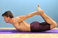 Bow yoga pose. Shirtless athletic man demonstrates a yoga bow pose on mat Stock Image