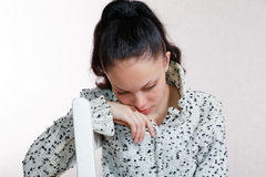 She bowed her head sitting on a  chair Royalty Free Stock Images
