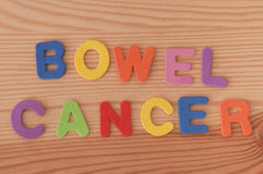 Bowel Cancer. The words bowel cancer made from foam letters on a wooden background stock photos