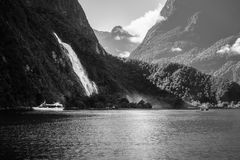 Bowen Falls at Milford Sound in black and white. A few boat cruises circling around the very powerful Bowen Falls at Milford Sound on a beautiful summer morning Stock Image