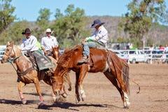 BOWEN-FLOD, QUEENSLAND, AUSTRALIEN - JUNI 10TH 2018: Cowboy som konkurrerar i den barbacka Bronchändelsen på rodeon för Bowen flo royaltyfri bild
