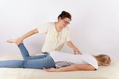 Bowen terapeut som ger en massagebehandling till en ung kvinna Royaltyfria Bilder