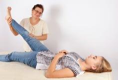 Bowen terapeut som ger en massagebehandling till en ung kvinna Arkivfoto