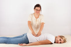 Bowen therapist treats a young girl`s back Royalty Free Stock Image