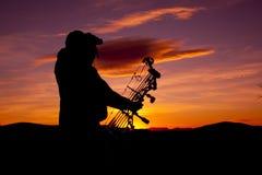 Bowhunter, das im Sonnenuntergang Glassing ist Lizenzfreie Stockfotografie