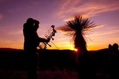 Bowhunter, das im Sonnenuntergang Glassing ist Stockbilder